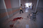 FILE - In this March 22, 2021, file photo, blood splatters the floor of a hospital in Atareb, a town in rural western Aleppo, Syria. Artillery shells fired from government areas killed at least five civilians and wounded medical staff when they landed in front of the hospital. Countries like Lebanon, Syria, Iraq, Lebanon and Yemen are all teetering on the brink of humanitarian catastrophe with an economic implosion that threatens to throw the region into even deeper turmoil.(AP Photo/Ghaith Alsayed, File)