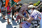 A woman shields herself from the midday sun as she awaits the start of a queer liberation march for Black Lives Matter and against police brutality, Sunday, June 28, 2020, in New York. (AP Photo/Kathy Willens)