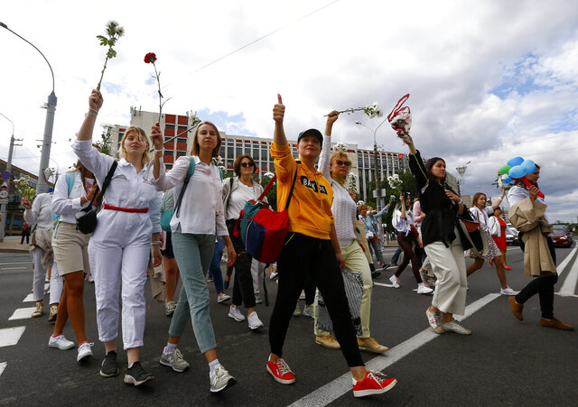 Belarusian women carry flowers on a rally in solidarity with protesters injured in the latest rallies against the results of the country's presidential election in Minsk, Belarus, Thursday, Aug. 13, 2020. Hundreds of people were back on the streets of Belarus' capital on Thursday morning, forming long