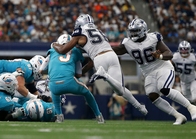 Miami Dolphins quarterback Josh Rosen (3) is sacked by Dallas Cowboys defensive end Robert Quinn (58) and defensive tackle Maliek Collins (96) in the second half of an NFL football game in Arlington, Texas, Sunday, Sept. 22, 2019. (AP Photo/Ron Jenkins)