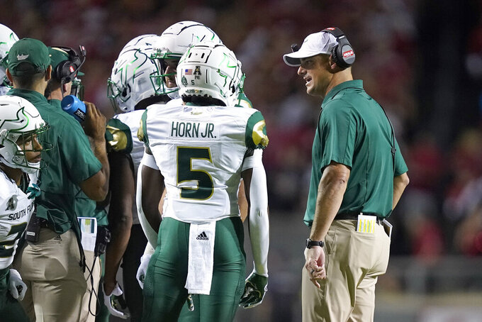 South Florida head coach Jeff Scott speaks with his team during the first half of an NCAA college football game against North Carolina State in Raleigh, N.C., Thursday, Sept. 2, 2021. (AP Photo/Gerry Broome)