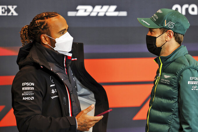 Aston Martin driver Sebastian Vettel of Germany, right, talks with Mercedes driver Lewis Hamilton of Britain during a press conference ahead of Sunday's Emilia Romagna Formula One Grand Prix, at the Imola track, Italy, Friday, April 16, 2021. (Xpbimages/Pool via AP)
