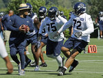 Seattle Seahawks defensive tackles Earl Mitchell (75) and Al Woods (72) work with defensive coordinator Ken Norton Jr., left, during NFL football training camp, Thursday, July 25, 2019, in Renton, Wash. (AP Photo/Ted S. Warren)