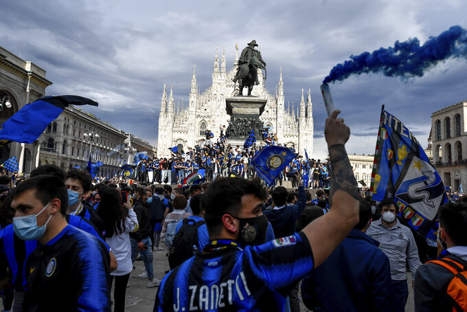 Inter Milan fans celebrate with flares and shout slogans in Piazza Duomo square in front of the gothic cathedral after Inter Milan won its first Serie A title in more than a decade after second-placed Atalanta drew 1-1 at Sassuolo, in Milan, Italy, Sunday, May 2, 2021. Atalanta needed to win to avoid Inter mathematically clinching the title with four matches remaining. It was Inter's first trophy since 2011 and the first Serie A title since 2010. (Claudio Furlan/LaPresse via AP)