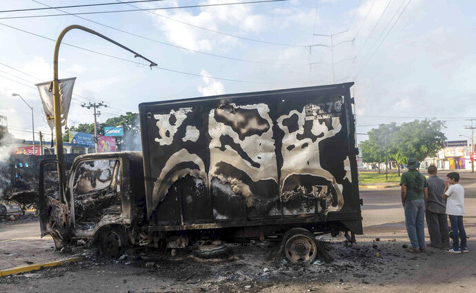 This Oct. 18, 2019 photo shows a burnt out truck used by gunmen smoldering on an intersection, a day after street battles between gunmen and security forces in Culiacan, Mexico. Mexican security forces backed off an attempt to capture a son of imprisoned drug lord Joaquin