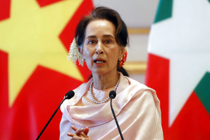 FILE - In this Dec. 17, 2019, file photo, Myanmar's former leader Aung San Suu Kyi speaks during a joint press conference with Vietnam's Prime Minister Nguyen Xuan Phuc after their meeting at the Presidential Palace in Naypyitaw, Myanmar. A court in Myanmar has agreed to change the venue for the trial of an Australian economist and advisor to Myanmar's ousted leader Aung San Suu Kyi accused of violating the Southeast Asian nation's official secrets law. (AP Photo/Aung Shine Oo, File)