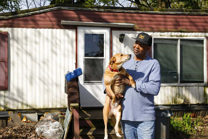 ADVANCE FOR PUBLICATION ON MONDAY, MAY 25, AND THEREAFTER - In this Friday, May 15, 2020, photo, Duane Daniels and his dog Chutki are shown at their home in Madison, Wis. The two have received help from the Dane County Humane Society's Pets for Life program. (Ruthie Hauge/The Capital Times via AP)