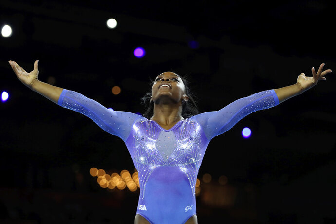 FILE - In this Oct. 13, 2019, file photo, Gold medalist Simone Biles of the United States performs on the floor in the women's apparatus finals at the Gymnastics World Championships in Stuttgart, Germany. Biles will headline a post-Olympic tour coming to more than 35 cities in late 2020. Biles said the all-female tour will be a mixture of gymnastics and entertainment and is designed to empower young athletes across the country. (AP Photo/Matthias Schrader)