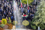 In this photo released by the official website of the Iranian Defense Ministry, officials and armed forces commanders pray and pay their respect over the flag draped coffin of Mohsen Fakhrizadeh, a scientist who was killed on Friday, in a funeral ceremony in Tehran, Iran, Monday, Nov. 30, 2020. Iran held the funeral service Monday for the slain scientist who founded its military nuclear program two decades ago, with the Islamic Republic's defense minister vowing to continue the man's work