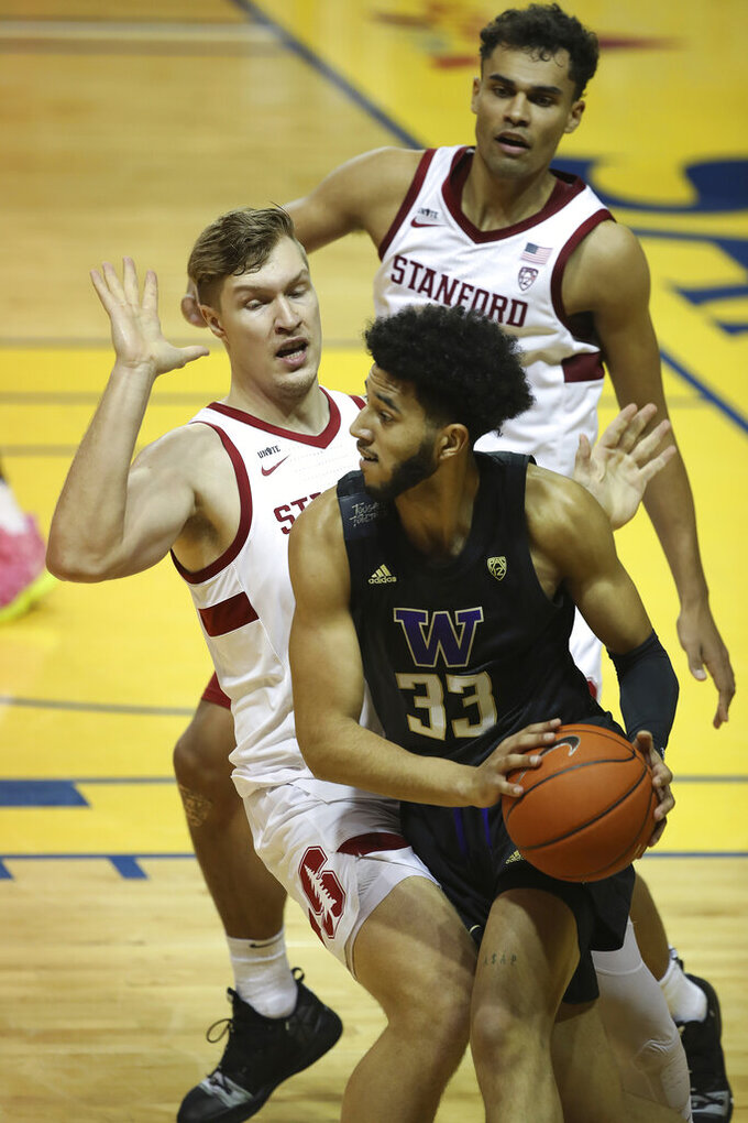 CORRECTS YEAR TO 2021 NOT 2020 - Stanford forward Lukas Kisunas, left, blocks Washington forward J'Raan Brooks (33) during the first half of an NCAA college basketball game in Santa Cruz, Calif., Thursday, Jan. 7, 2021. (AP Photo/Josie Lepe)