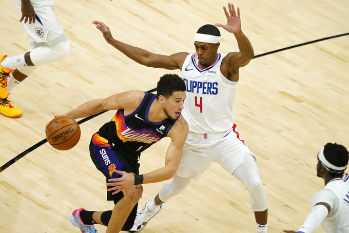 Phoenix Suns guard Devin Booker (1) drives as Los Angeles Clippers guard Rajon Rondo (4) defends during the first half of an NBA basketball game, Wednesday, April 28, 2021, in Phoenix. (AP Photo/Matt York)