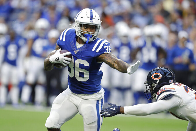 Indianapolis Colts running back Charcandrick West (36) runs past Chicago Bears defensive back Sherrick McManis for a touchdown during the first half of an NFL preseason football game Saturday, Aug. 24, 2019, in Indianapolis. (AP Photo/Michael Conroy)