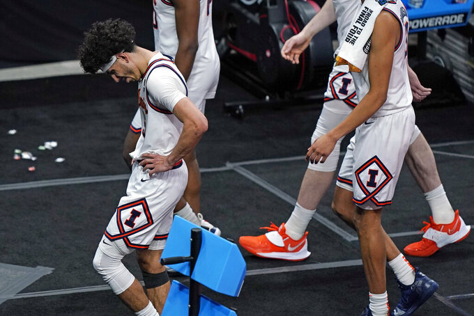 Illinois' Andre Curbelo, left, leaves the court after a college basketball game against Loyola in the second round of the NCAA tournament at Bankers Life Fieldhouse in Indianapolis Sunday, March 21, 2021. Loyola upset Illinois 71-58. (AP Photo/Mark Humphrey)