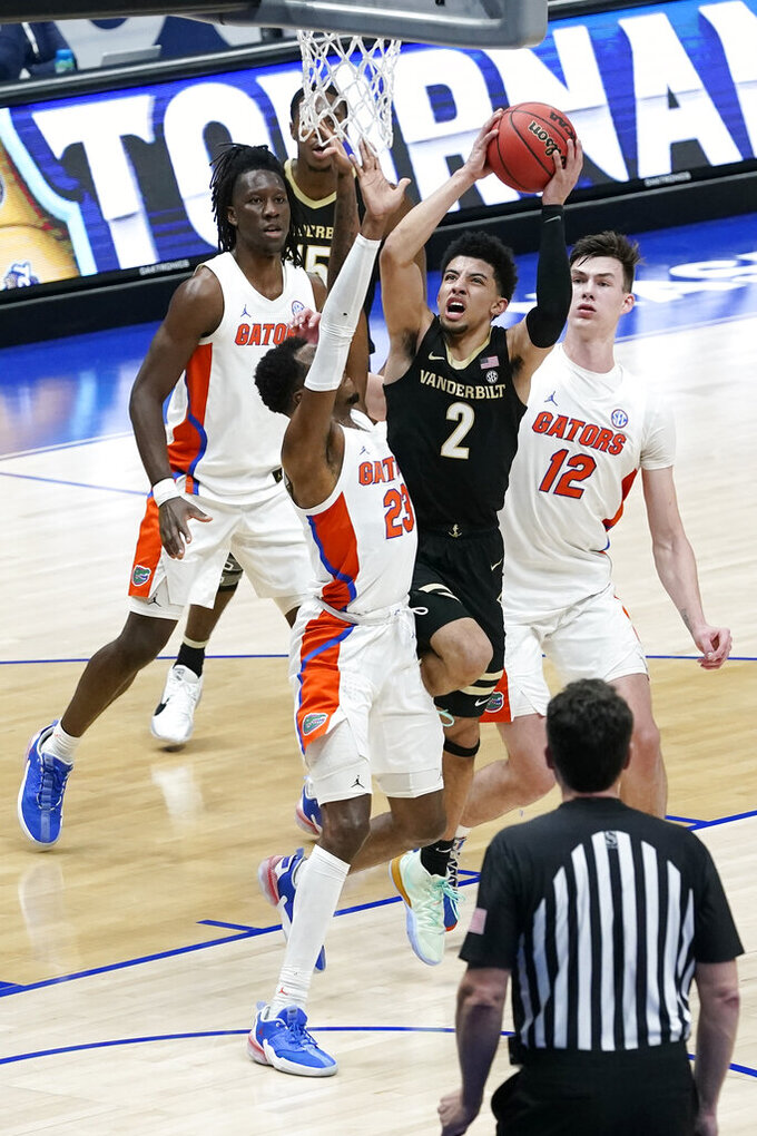 Vanderbilt's Scotty Pippen Jr. (2) drives against Florida's Scottie Lewis (23) and Colin Castleton (12) in the second half of an NCAA college basketball game in the Southeastern Conference Tournament Thursday, March 11, 2021, in Nashville, Tenn. (AP Photo/Mark Humphrey)