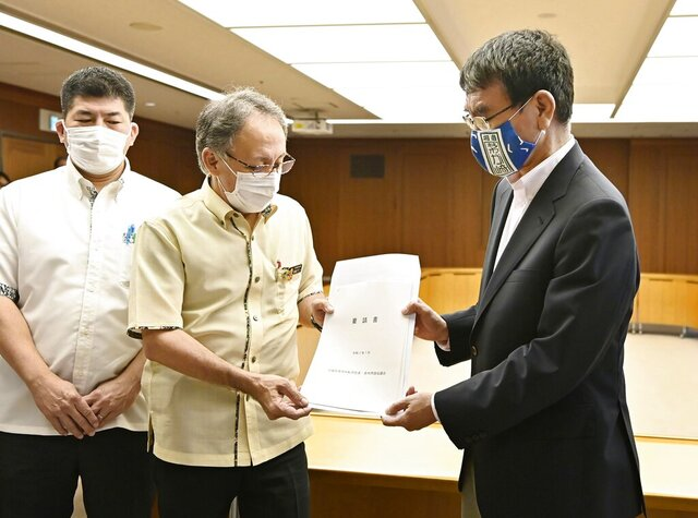 Okinawa Gov. Denny Tamaki, center, and Japanese Defense Minister Taro Kono, right, hold Okinawa's request document during their meeting at the Defense Ministry in Tokyo, Wednesday, July 15, 2020.  Gov. Tamaki urged Japan's government to pressure the U.S. military to better guard against an escalating coronavirus outbreak that has infected more than 130 Marines stationed on the southern Japanese island, triggering fear of infections spreading outside of the bases.(Ren Onuma/Kyodo News via AP)