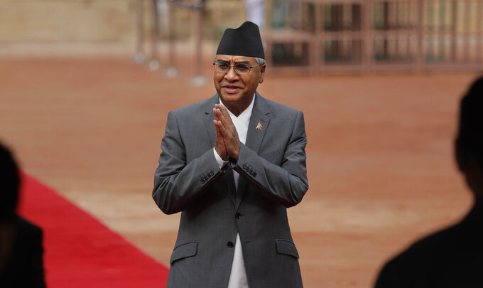 In this Thursday, Aug. 24, 2017, file photo, then Nepalese Prime Minister Sher Bahadur Deuba greets Indian ministers during his ceremonial reception at the Indian presidential palace in New Delhi, India. Deuba, a veteran politician was appointed Nepal's prime minister for the fifth time on Tuesday, a day after the Supreme Court reinstated the House of Representatives and upheld his claim to be the new leader. (AP Photo/Manish Swarup)