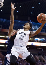 Grand Canyon's Carlos Johnson (11) drives to the basket against Nevada's Tre'Shawn Thurman (0) during the first half of an NCAA college basketball game Sunday, Dec. 9, 2018, in Phoenix. (AP Photo/Darryl Webb)
