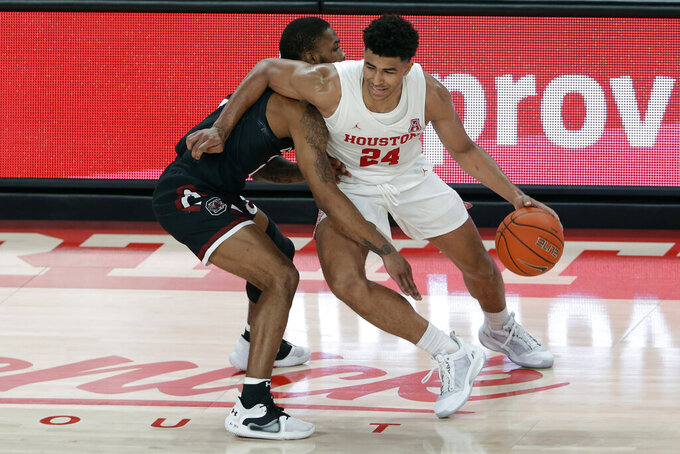 Houston guard Quentin Grimes (24) drives around South Carolina guard Seventh Woods during the second half of an NCAA college basketball game Saturday, Dec. 5, 2020, in Houston. (AP Photo/Michael Wyke)