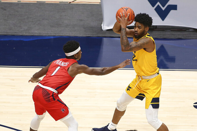 West Virginia guard Taz Sherman (12) is defended by Richmond guard Blake Francis (1) during the first half of an NCAA college basketball game Sunday, Dec. 13, 2020, in Morgantown, W.Va. (AP Photo/Kathleen Batten)