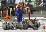 FILE - In this Nov. 4, 2018 file photo, officials move an engine recovered from the crashed Lion Air jet for further investigation in Jakarta, Indonesia. The brand new Boeing 737 MAX 8 jet plunged into the Java Sea just minutes after takeoff from Jakarta early on Oct. 29, killing all of its passengers on board. The FAA's oversight duties are coming under greater scrutiny after deadly crashes involving Boeing 737 Max jets owned by airlines in Ethiopia and Indonesia, killing a total of 346 people. (AP Photo/Achmad Ibrahim, File)