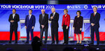 From left, Democratic presidential candidates entrepreneur Andrew Yang, former South Bend Mayor Pete Buttigieg, Sen. Bernie Sanders, I-Vt., former Vice President Joe Biden, Sen. Elizabeth Warren, D-Mass., Sen. Amy Klobuchar, D-Minn., and businessman Tom Steyer stand on stage Friday, Feb. 7, 2020, stand on stage before the start of a Democratic presidential primary debate hosted by ABC News, Apple News, and WMUR-TV at Saint Anselm College in Manchester, N.H. (AP Photo/Charles Krupa)