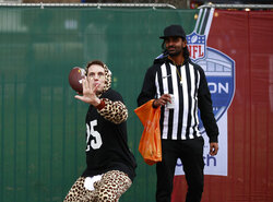 A fan shapes-up to pass the ball as he arrives for an NFL football game between the Miami Dolphins and the Jacksonville Jaguars at the Tottenham Hotspur stadium in London, England, Sunday, Oct. 17, 2021. (AP Photo/Ian Walton)