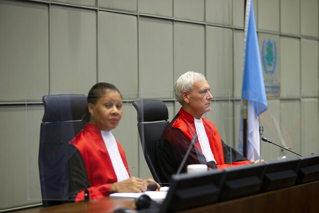 Presiding judge David Re, right, and judge Janet Nosworthy, left, pose for pictures prior to a session of the United Nations-backed Lebanon Tribunal where it is scheduled to hand down it's sentencing on Salim Jamil Ayyash, a member of the Hezbollah militant group who was convicted of involvement in the assassination of former Lebanese Prime Minister Rafik Hariri and 21 others 15 years ago, in Leidschendam, Netherlands, Friday Dec. 11, 2020. Ayyash is not in custody and is unlikely to serve any sentence. (AP Photo/Peter Dejong, Pool)