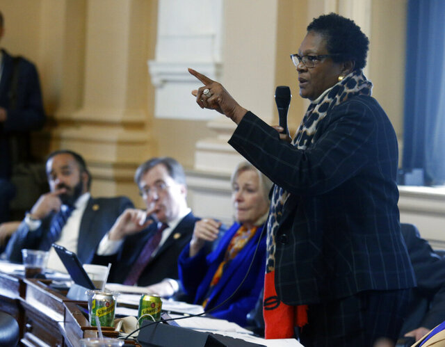 Del. Delores McQuinn, D-Richmond, right, gives an impassioned speech for passage of HB 1537, her bill that would allow the removal, relocation or altering memorials to war veterans, during the floor session of the Virginia House of Delegates inside the State Capitol in Richmond, VA Tuesday, Feb. 11, 2020. The bill passed, 53-46. Looking on are, from left, Del. Jeff Bourne, D-Richmond, Del. Rip Sullivan, D-Fairfax and Del. Kathleen Murphy, D-Fairfax. (Bob Brown/Richmond Times-Dispatch via AP)