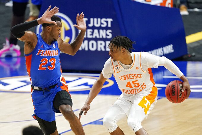 Tennessee's Keon Johnson (45) moves past Florida's Scottie Lewis (23) in the second half of an NCAA college basketball game in the Southeastern Conference Tournament Friday, March 12, 2021, in Nashville, Tenn. (AP Photo/Mark Humphrey)