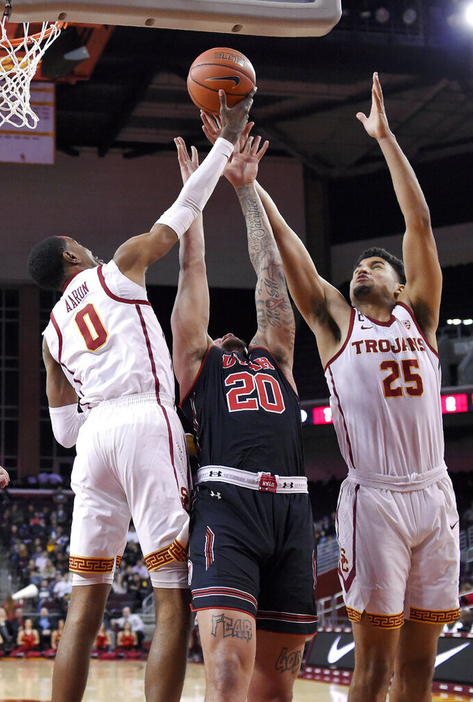 Southern California guard Shaqquan Aaron, left, and forward Bennie Boatwright, right, and Utah forward Timmy Allen reach for a rebound during the first half of an NCAA college basketball game Wednesday, Feb. 6, 2019, in Los Angeles. (AP Photo/Mark J. Terrill)