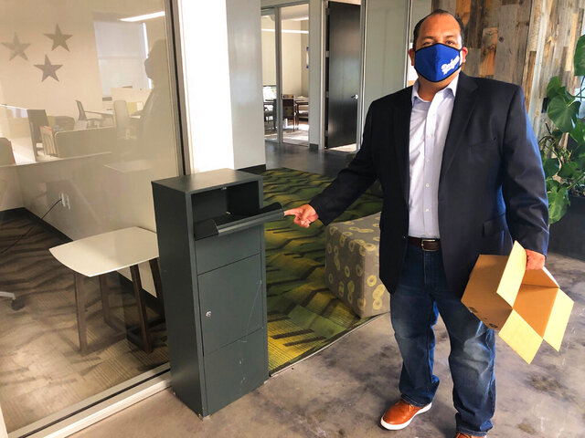 FILE — In this Oct. 20, 2020, file photo, California Republican Party spokesman Hector Barajas demonstrates how to use one of the party's unofficial ballot drop boxes, in Sacramento, Calif. California Attorney General Xavier Becerra announced Friday, Nov. 20, that he dropped a lawsuit against the state Republican Party that was seeking the names and contact information of every person who used one of the state Republican party's unofficial ballot drop boxes. (AP Photo/Adam Beam, File)