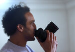Mahmoud Abu Zaid, a photojournalist known as Shawkan, kisses his colleague's camera at his home in Cairo, Egypt, Monday, March 4, 2019. Shawkan was released after five years in prison. (AP Photo/Amr Nabil)