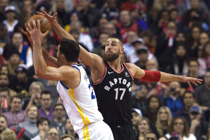 Toronto Raptors center Jonas Valanciunas (17) tries to block a shot by Golden State Warriors center Zaza Pachulia (27) during the first half of an NBA basketball game Saturday, Jan. 13, 2018, in Toronto. (Cole Burston/The Canadian Press via AP)