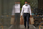 A man wearing a face mask to help protect from the coronavirus carries goody bags as he walks by a row of bicycles parked along a pavement in Beijing, Monday, Sept 13, 2021. (AP Photo/Andy Wong)