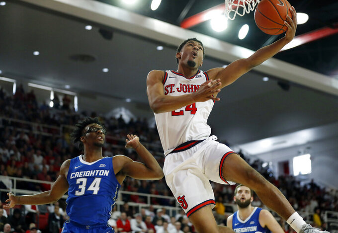 St. John's guard Nick Rutherford (24) goes up for two points as Creighton guard Denzel Mahoney (34) looks on during the second half of an NCAA college basketball game, Sunday, March 1, 2020, in New York. St. Johns upset Creighton 91-71. (AP Photo/Kathy Willens)