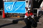An anti-government protester sits near the United Nations flag on a tent in Tahrir Square during ongoing anti-government protests in Baghdad, Iraq, Saturday, Feb. 1, 2020. (AP Photo/Khalid Mohammed)