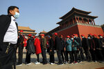 A man wearing a face mask to help curb the spread of the coronavirus walks by masked tourists lining up to enter Forbidden City in Beijing, Sunday, Oct. 25, 2020. With the outbreak of COVID-19 largely under control within China's borders, the routines of normal daily life have begun to return for its citizens. (AP Photo/Andy Wong)