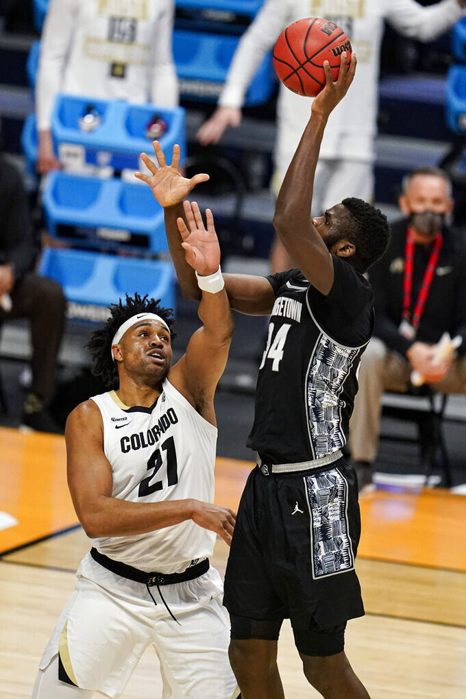 Georgetown center Qudus Wahab (34) shoots over Colorado forward Evan Battey (21) in the first half of a first-round game in the NCAA men's college basketball tournament at Hinkle Fieldhouse in Indianapolis, Saturday, March 20, 2021. (AP Photo/Michael Conroy)