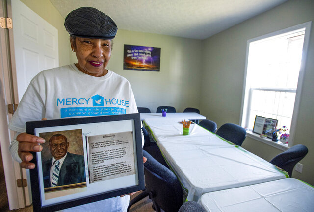 In this Saturday Jan. 4, 2020. photo, Mary Boone holds a framed obit of her uncle John Wesley McCree in his former home, that is now the Pathway House in the Washington Park neighborhood in Montgomery, Ala. (Mickey Welsh/Montgomery Advertiser via AP)