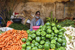 A vegetable vendor wearing a face mask partly covering her face waits for customers in Bengaluru, India, Sunday, Oct. 11, 2020. India's confirmed coronavirus toll crossed 7 million on Sunday with a number of new cases dipping in recent weeks, even as health experts warn of mask and distancing fatigue setting in. (AP Photo/Aijaz Rahi)