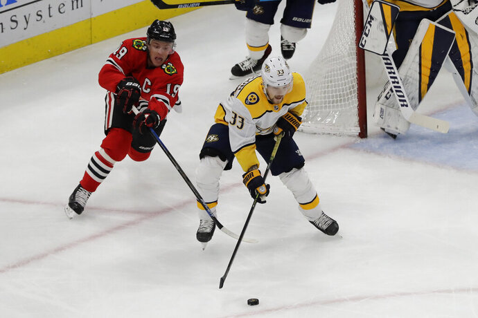 Nashville Predators right wing Viktor Arvidsson, right, controls the puck against Chicago Blackhawks center Jonathan Toews during the first period of an NHL hockey game in Chicago, Thursday, Jan. 9, 2020. (AP Photo/Nam Y. Huh)