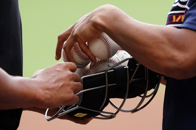 Home plate umpire Jeremy Rehak, left, stocks up on baseballs before the start of a spring training baseball game between the Boston Red Sox and the Atlanta Braves on Monday, March 29, 2021, in North Port, Fla. (AP Photo/John Bazemore)