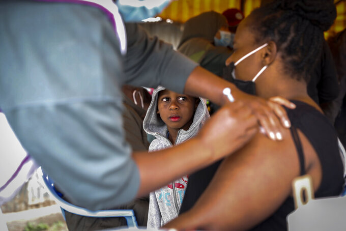 A Kenyan woman receives a dose of AstraZeneca coronavirus vaccine donated by Britain, as her son watches, at the Makongeni Estate in Nairobi, Kenya Saturday, Aug. 14, 2021. In late June, the international system for sharing coronavirus vaccines sent about 530,000 doses to Britain – more than double the amount sent that month to the entire continent of Africa. It was the latest example of how a system that was supposed to guarantee low and middle-income countries vaccines is failing, leaving them at the mercy of haphazard donations from rich countries. (AP Photo/Brian Inganga)