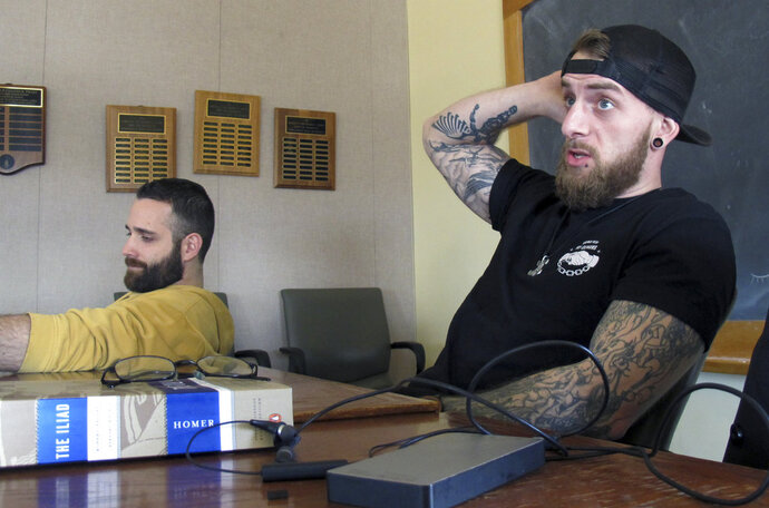 In this Feb. 12, 2018 photo, University of Vermont student veterans Thomas Moore, left, and Dan Wright, participate in a class studying Homer's