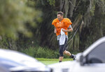 "FILE - In this May 19, 2020, file photo, Tampa Bay Buccaneers NFL football quarterback Tom Brady runs across the field at Berkeley Preparatory School in Tampa, Fla. With coaches and players scattered and team facilities shut by the NFL because of the COVID-19 pandemic, video meetings helped the league act as if business continued as usual. ""Walking through and practicing is the best way to teach,"" Tampa Bay coach Bruce Arians said. ""So those are valuable reps missed. I don't know how we'll make them up. Hopefully we'll get some extra time in practice in camp; a few extra days would help."