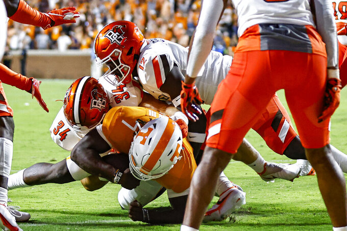 Tennessee quarterback Joe Milton III (7) dives across the goal line as he's hit by Bowling Green linebackers Brock Horne (34) and JB Brown (12) during the first half of an NCAA college football game Thursday, Sept. 2, 2021, in Knoxville, Tenn. (AP Photo/Wade Payne)