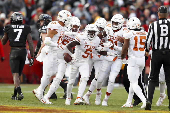 Texas defensive back D'Shawn Jamison (5) celebrates with teammates after intercepting a pass during the first half of an NCAA college football game against Iowa State, Saturday, Nov. 16, 2019, in Ames, Iowa. (AP Photo/Charlie Neibergall)