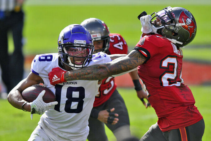 Minnesota Vikings wide receiver Justin Jefferson (18) stiff arms Tampa Bay Buccaneers cornerback Carlton Davis (24) after a catch during the first half of an NFL football game Sunday, Dec. 13, 2020, in Tampa, Fla. (AP Photo/Jason Behnken)