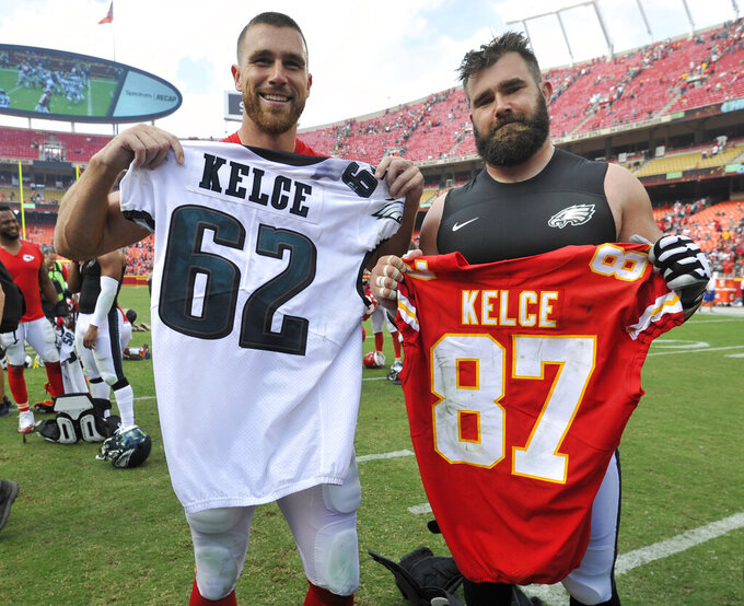 FILE - Kansas City Chiefs tight end Travis Kelce, left, and his brother, Philadelphia Eagles center Jason Kelce (62), exchange jerseys following an NFL football game in Kansas City, Mo., in this Sunday, Sept. 17, 2017, file photo. Travis Kelce and Jason Kelce are both three-time All-Pro picks and each has won a Super Bowl. The big advantage: Travis is 2-0 against his older brother. The Kelce brothers face off one more time when the Philadelphia Eagles (1-2) host the Kansas City Chiefs (1-2) on Sunday, Nov. 3, 2021. (AP Photo/Ed Zurga, File)