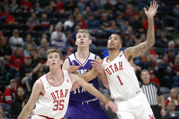 Weber State forward Tim Fuller, center, battles under the boards with Utah's Branden Carlson (35) and Timmy Allen (1) in the first half during an NCAA college basketball game Saturday, Dec. 14, 2019, in Salt Lake City. (AP Photo/Rick Bowmer)